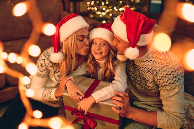 Joyeux noel et bonne année! une famille heureuse attend le nouvel an en chapeaux de père noël échangeant des cadeaux les uns avec les autres. maman et papa embrassent une jolie fille