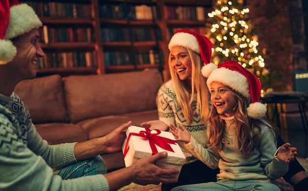 Joyeux noel et bonne année! une famille heureuse attend le nouvel an en chapeaux de père noël échangeant des cadeaux les uns avec les autres.