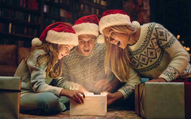 Joyeux noël et bonne année! une famille heureuse attend la nouvelle année dans les chapeaux du père noël. les parents présentent un coffret cadeau à leur charmante fille. lumière magique de l'intérieur.