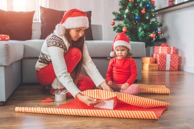 Joyeux noel et bonne année. une femme sérieuse et concentrée s'assoit et couvre la boîte de papier. petite fille regarde le processus. elle est paisible. ils portent tous les deux un chapeau. ils préparent des cadeaux.