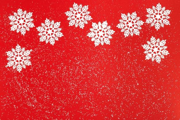 Joyeux noël et bonne année fond avec des flocons de neige sur rouge brillant
