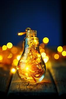 Joyeux noel et bonne année. guirlande de noël dans un bocal en verre sur une table en bois. mise au point sélective.