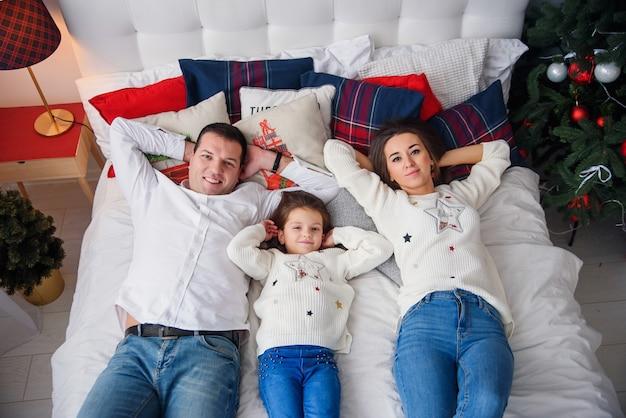 Joyeux noël et bonne année happy family couché dans son lit près de bel arbre de noël.
