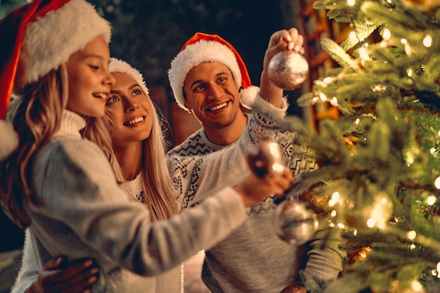Joyeux noel et bonne année! héhé, célébrant les vacances d'hiver à la maison. maman, papa et fille décorant l'arbre du nouvel an.