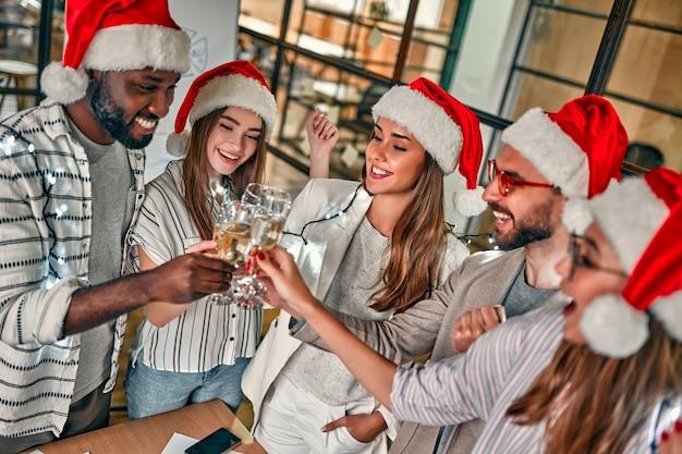 Joyeux noel et bonne année! les jeunes créatifs multiraciaux célèbrent les vacances dans un bureau moderne. un groupe de jeunes gens d'affaires boit du champagne en coworking.