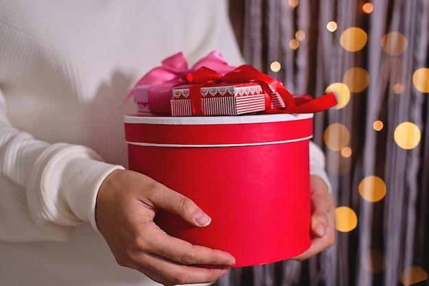Joyeux noël ou bonne année mains de femme tenant une boîte-cadeau rouge se bouchent sur fond scintillant