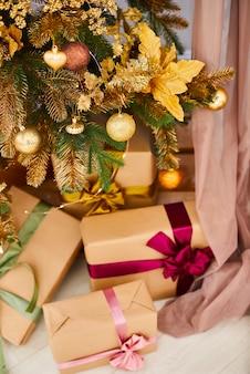 Joyeux noël et bonne année! nombreux cadeaux sous le sapin de noël décorés de jouets en or. boîtes décorées avec des cadeaux sous un arbre de vacances à l'intérieur