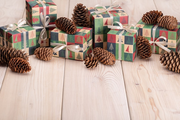 Joyeux noel et bonne année. pommes de pin et cadeaux en papier élégant