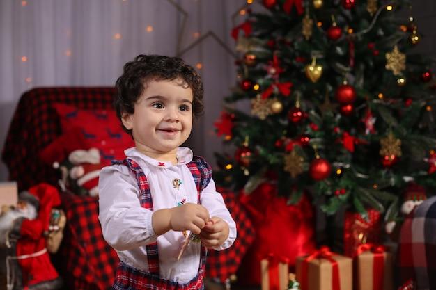 Joyeux noel et bonne année! portrait d'un enfant ému en costume de nouvel an dans la salle décorée.