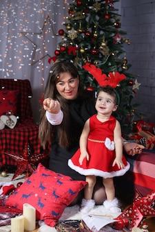 Joyeux noel et bonne année! portrait d'un enfant ému en costume de nouvel an avec sa mère dans la salle décorée.