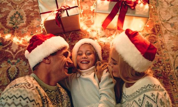 Joyeux noel et bonne année! vue de dessus de la famille heureuse est allongée sur le sol avec des coffrets cadeaux et une guirlande à proximité.