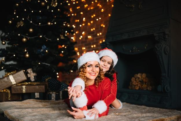 Joyeux noël et bonnes fêtes! belle mère avec petite fille en costumes de noël passent du temps ensemble près de l'arbre de noël.