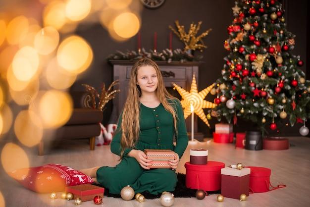 Joyeux noël et bonnes fêtes. joyeuse jolie adolescente ouvrant des cadeaux.