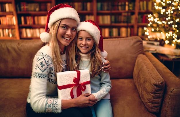 Joyeux noël et bonnes fêtes! joyeuse maman et sa jolie fille fille échangeant des cadeaux. parent et petit enfant s'amusant près de l'arbre à l'intérieur. famille aimante avec des cadeaux dans la chambre.