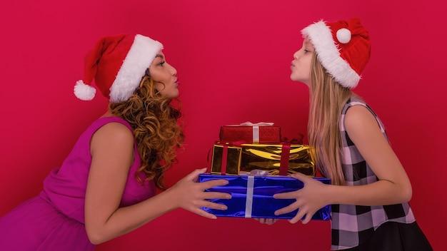Joyeux noël et bonnes vacances. joyeuse maman et sa fille mignonne tenant un cadeau de noël