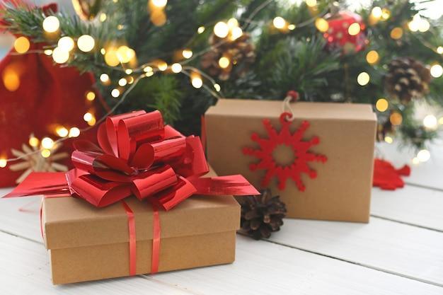 Joyeux noël cadeaux de noël et surprises à côté de branches d'arbre de noël et de lumières brillantes