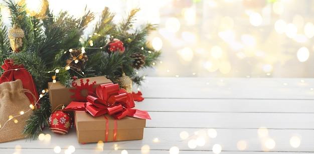 Joyeux noël cadeaux et surprises sur une table en bois blanche à côté des branches d'un arbre de noël