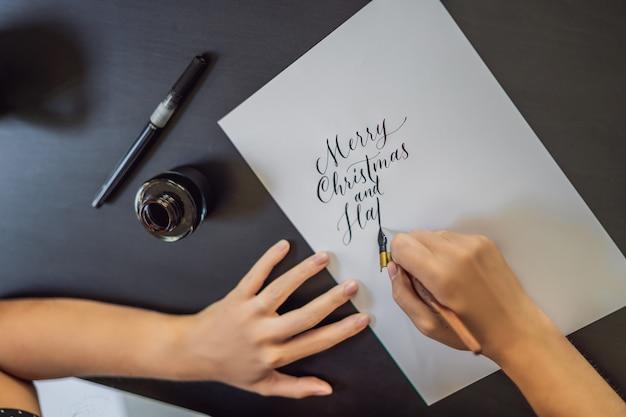 Joyeux noël. calligraphe jeune femme écrit une phrase sur du papier blanc