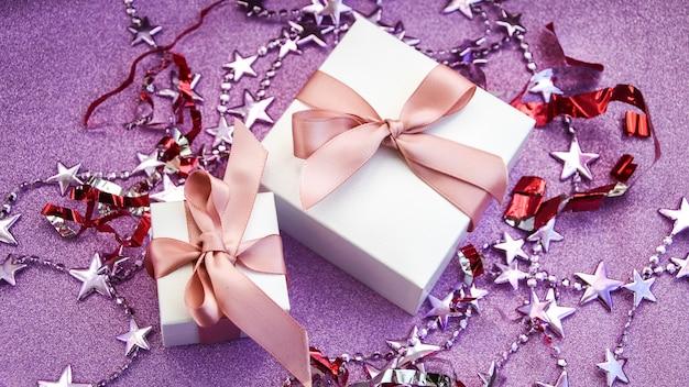 Joyeux noël ou carte de saint valentin faite de décorations coffrets cadeaux blancs avec ruban rose spar...