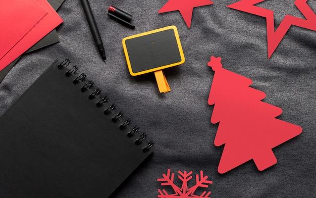 Joyeux noël concept, livre noir, papier rouge et stylo sur toile grise