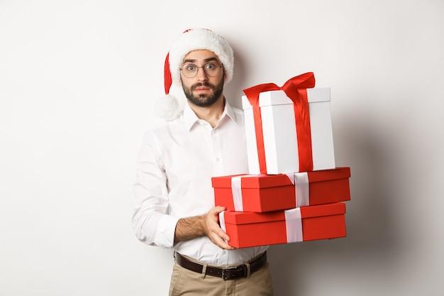 Joyeux noël, concept de vacances. homme confus en bonnet de noel tenant une pile de cadeaux, a trouvé des cadeaux sous l'arbre de noël, debout sur fond blanc.