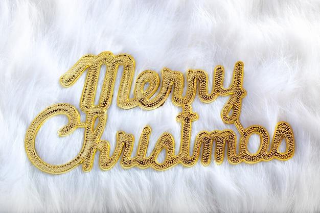 Joyeux noël écrit en or sur la fourrure blanche