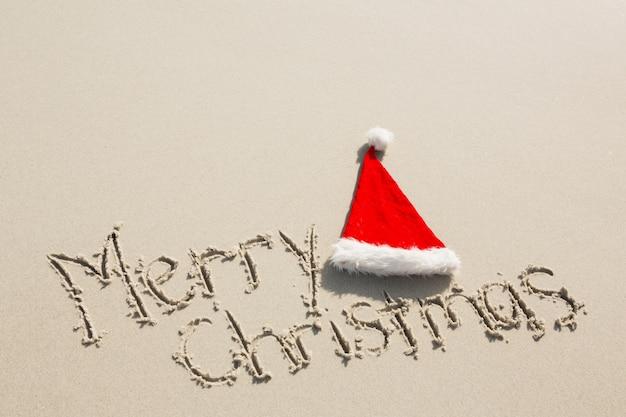 Joyeux noël écrit sur le sable avec le chapeau de santa