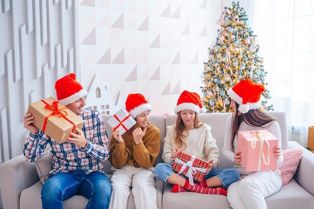 Joyeux noël. famille de quatre personnes avec des cadeaux à noël à la maison