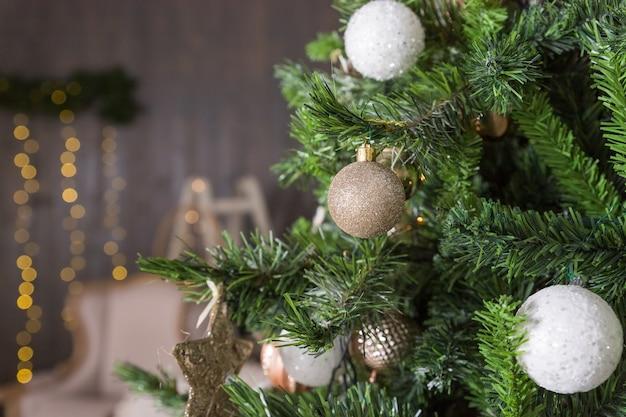 Joyeux noël. fond de vacances d'hiver avec arbre de noël avec boule or et blanc, ruban, guirlandes et flocons de neige. scène de noël branches de sapin de noël avec des décorations boules de verre colorées