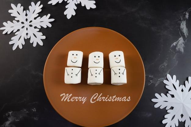 Joyeux noël guimauves bonhomme de neige et flocons de neige sur le côté