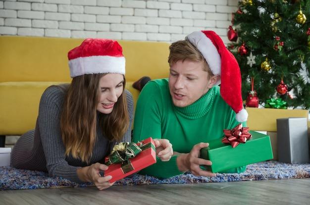 Joyeux noël. jeune couple amoureux avec bonnet rouge montrant la boîte-cadeau et pose ensemble