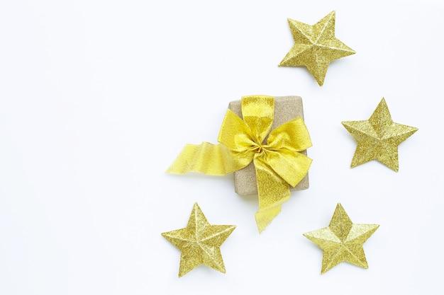 Joyeux noël et joyeuses fêtes, composition de noël. coffret cadeau avec des décorations étoiles dorées sur fond blanc.