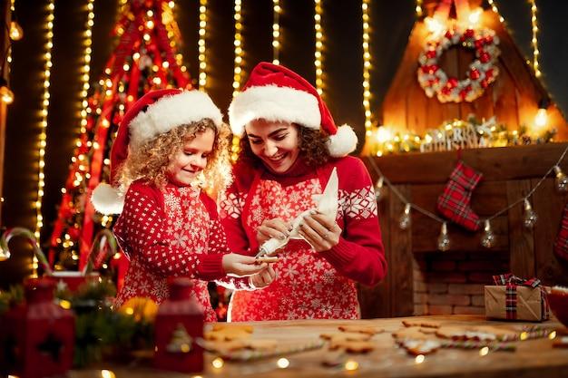 Joyeux noël et joyeuses fêtes. enthousiaste mignonne petite fille frisée et sa sœur aînée à chapeaux de pères noël cuisiner des biscuits de noël