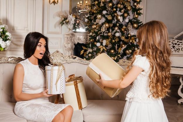 Joyeux noël et joyeuses fêtes. joyeuse maman et sa fille fille mignonne échangeant des cadeaux en piano intérieur classique blanc et un arbre de noël décoré. nouvel an