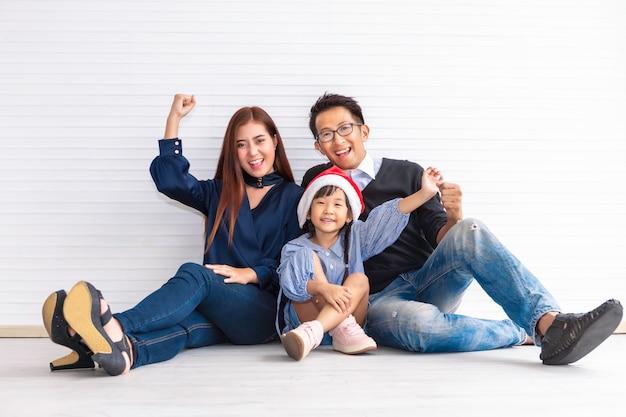 Joyeux noël et joyeuses fêtes! joyeux parent et sa jolie fille souriante et assise sur le sol.