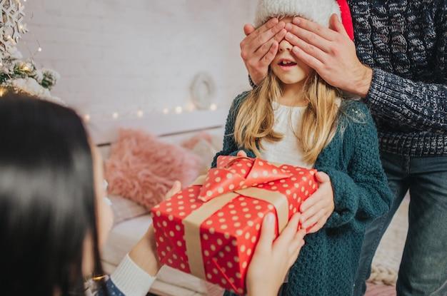 Joyeux noël et joyeuses fêtes mère gaie père et sa jolie fille fille échangeant des gif