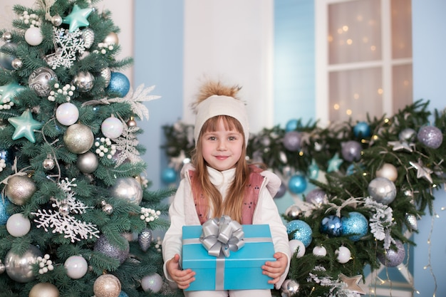 Joyeux noël, joyeuses fêtes! surface. petite fille avec un cadeau sur le porche de la maison près de sapin de noël. l'enfant est assis sur une véranda décorée pour noël et joue dans la cour d'hiver. l'enfant ouvre le cadeau.