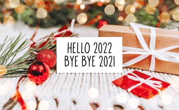 Joyeux noël et joyeux nouvel an concept avec coffrets cadeaux et carte de voeux avec texte bonjour 2022 bye bye 2021