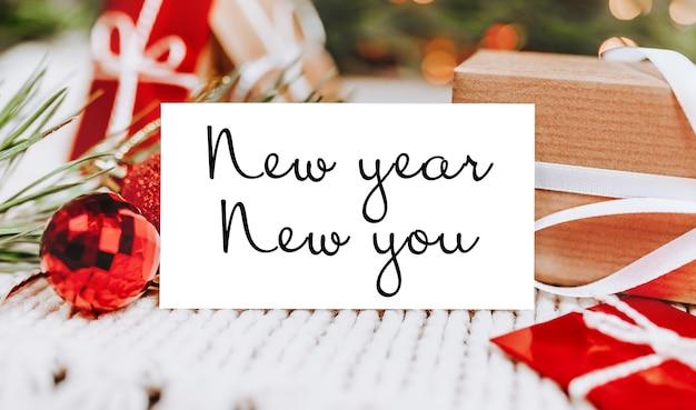 Joyeux noël et joyeux nouvel an concept avec coffrets cadeaux et carte de voeux avec texte nouvel an nouveau vous