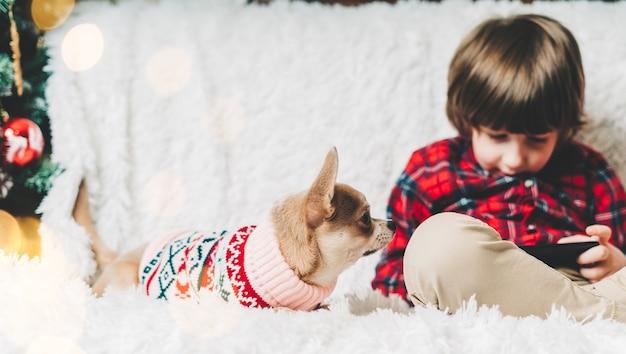 Joyeux noël joyeux petit enfant et chiot en pull jouant à l'étreinte et s'amusant sur le canapé avec