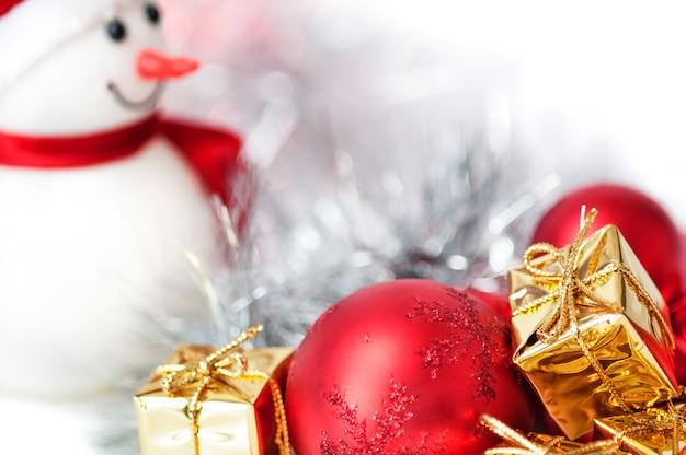 Joyeux noël, nouvel an, bonhomme de neige, cadeaux dans des boîtes dorées et des boules rouges sur fond de bokeh bleu et blanc.