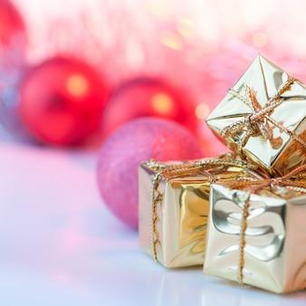 Joyeux noël, nouvel an, cadeaux dans des boîtes en or, boules de noël rouges dans le coin droit. bokeh de fond.