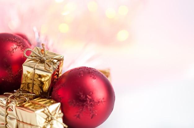 Joyeux noël, nouvel an, cadeaux dans des boîtes en or, des boules de noël rouges sont empilées dans le coin gauche. bokeh de fond.