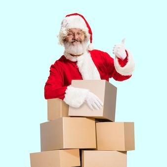 Joyeux noël père noël sur fond bleu studio. modèle masculin de race blanche en costume de fête traditionnelle. concept de vacances, nouvel an, humeur hivernale, cadeaux. ventes. montrant le pouce vers le haut.