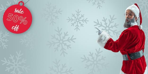 Joyeux noël père noël sur fond gris studio. modèle masculin de race blanche en costume de fête traditionnelle. concept de vacances, nouvel an, humeur hivernale, cadeaux. surprenant, concept de vente.