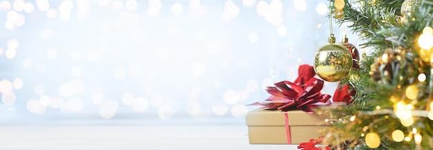 Joyeux noël et surprises sur une table blanche à côté de branches d'arbre de noël et de lumières