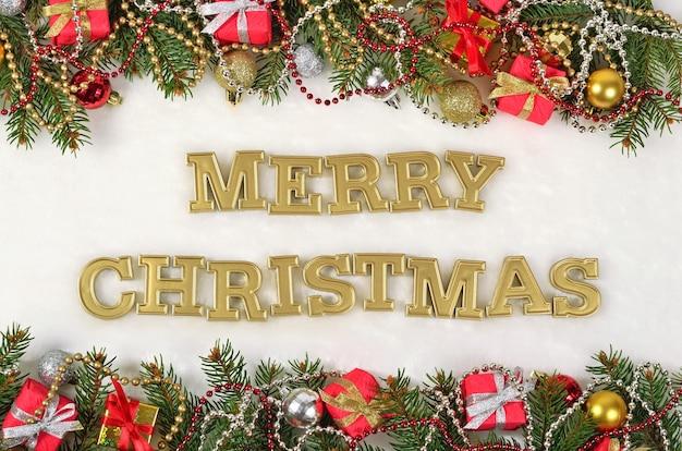 Joyeux noël texte d'or et branche d'épinette et décorations de noël sur fond blanc
