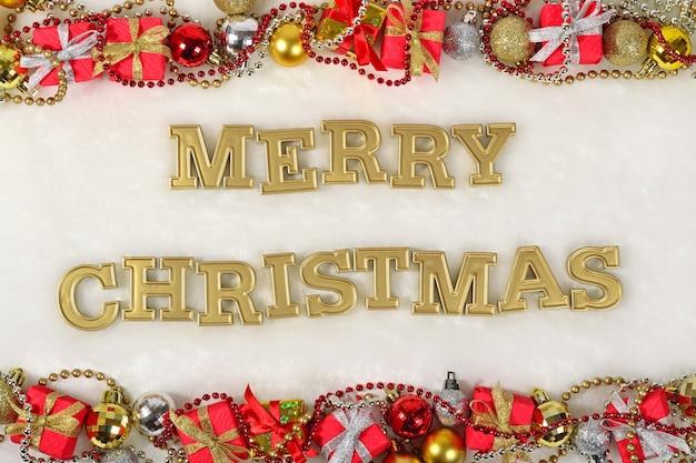 Joyeux noël texte d'or et décorations de noël sur fond blanc