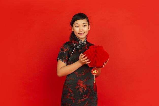 Joyeux nouvel an chinois 2020. portrait de jeune fille asiatique isolé sur fond rouge. le modèle féminin en vêtements traditionnels a l'air heureux et souriant avec une décoration. célébration, vacances, émotions.