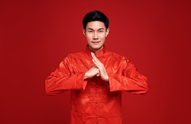 Joyeux nouvel an chinois. bel homme asiatique geste de félicitation sur le rouge.